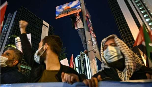 A protester holds a poster of Al-Aqsa mosque during a demonstration against Israel in front of theIs
