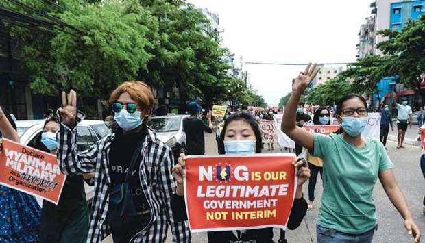 Protesters hold up the three finger salute as they march with placards during a demonstration agains
