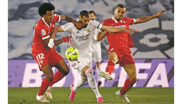 Real Madrid's Karim Benzema (centre) vies for the ball with Sevilla's Jules Kounde (left) and Joan J
