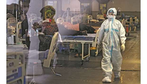 A health worker wearing a protective gear walks past Covid-19 patients inside a banquet hall tempora