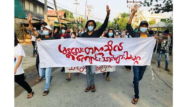 Students hold a banner and flash the three-finger salute as they take part in a protest against Myan