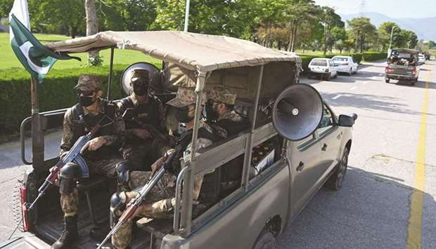 Army soldiers patrol on a street in Islamabad to implement new restrictions imposed as a preventativ