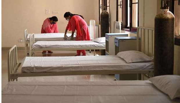 Health workers arrange beds for Covid-19 Coronavirus patients at a care centre in Amritsar