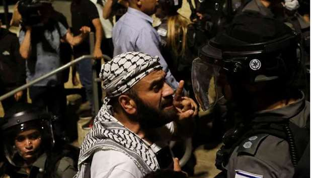 A Palestinian man gestures as he argues with an Israeli border policeman by the entrance to Jerusale