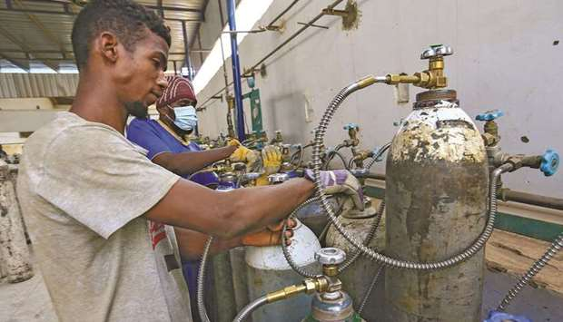 Workers prepare oxygen cylinders for coronavirus disease (Covid-19) patients inside the Sudanese Liq