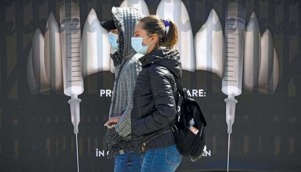People wearing protection masks walk by a banner showing syringes as vampire fangs during the vaccin