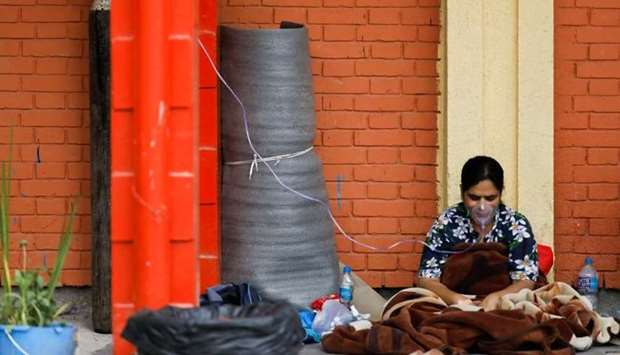 A patient receives oxygen as she waits outside the passage of a hospital due to a lack of free beds