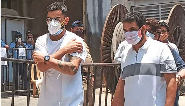 Indian cricket captain Virat Kohli clutches his arm as he walks out after receiving a dose of the Co