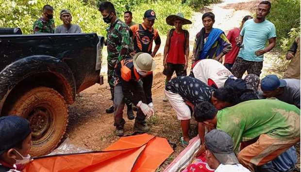 Rescuers retrieving bodies after a landslide at a gold mine in south Solok, West Sumatra province, w