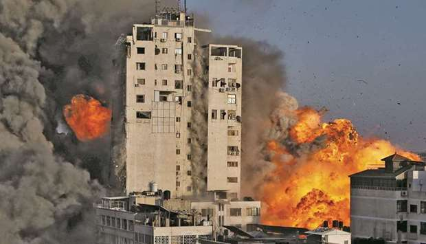 Smoke and flames rise from a tower building as it is destroyed by Israeli air strikes amid a flare-u