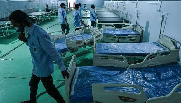 Volunteers arrange beds for patients at the Ramleela Maidan ground temporarily converted into a Covi