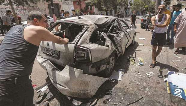 Palestinians inspect a destroyed vehicle in the aftermath of an Israeli air strike in Gaza City, on