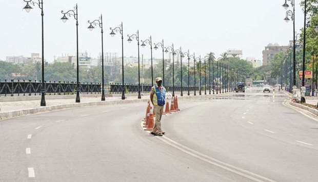 Police stand guard on a deserted street as the government imposed 10-day lockdown to curb the spread