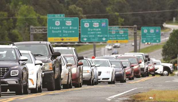 Scores of vehicles line up to enter a gasoline station as demand for fuel surges following the cyber