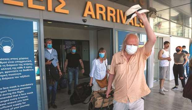 A man waves his hat as passengers arriving yesterday from Germany and Switzerland exit the terminal