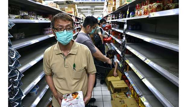 Customers rush to buy instant noodles after the government advised people to reduce leaving their ho