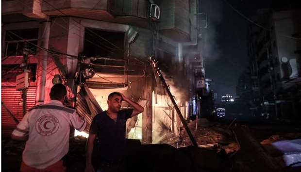 A Palestinian man is in disbelief at the terrifying scene unfolding before him as firefighters searc