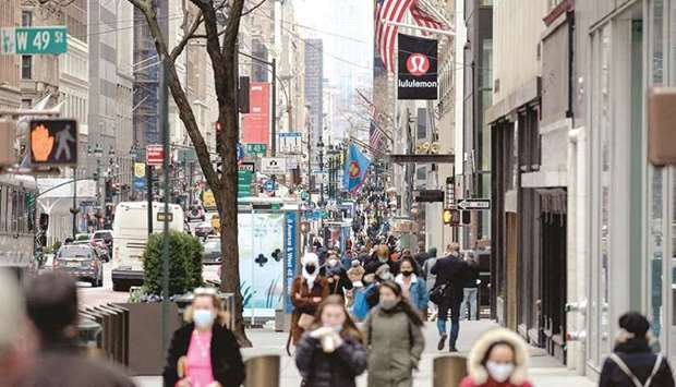 People walk on a busy 5th Avenue in midtown Manhattan. The prevailing scenario for the US recovery o