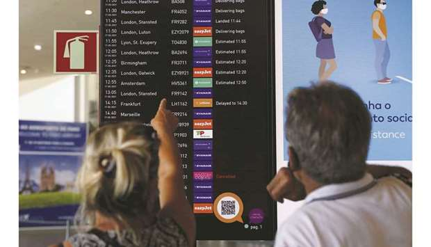 People watch a Faro Airport arrivals screen display information on the first day that Britons are al