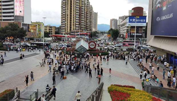 People stand near the 300-metre high SEG Plaza after it began to shake, in Shenzhen in China's south