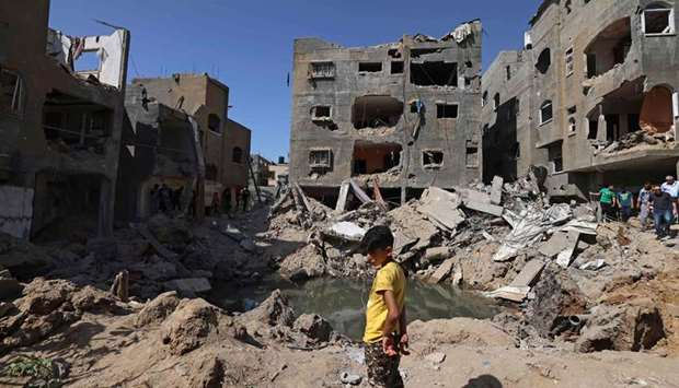 A Palestinian child stands amidst the rubble of buildings, destroyed by Israeli strikes, in Beit Han