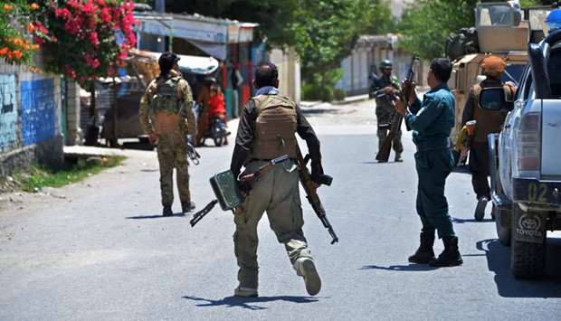 Members of Afghan security forces patrol a street during an ongoing clash between Taliban and Afghan