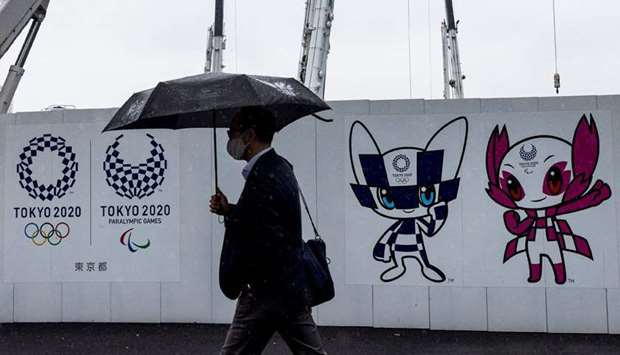 A pedestrian walks past a Tokyo 2020 Olympic and Paralympic Games decoration board bearing illustrat
