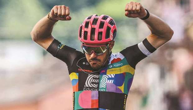 Team EF Education rider Italy's Alberto Bettiol celebrates as he crosses the finish line to win the
