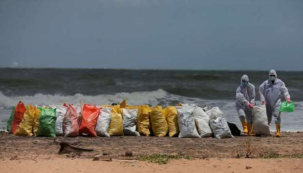 Sri Lankan navy members remove debris washed off to a beach from the MV X-Press Pearl container ship