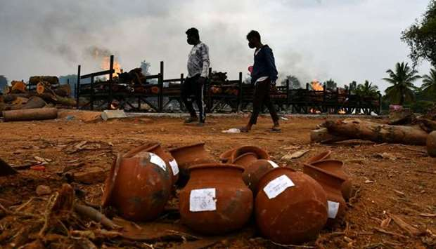 Men walk past burning pyres of persons who died due to the coronavirus disease (COVID-19), at a crem