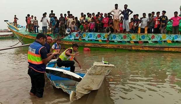 Policemen inspect a speed boat that was carrying passengers when it collided with a vessel transport