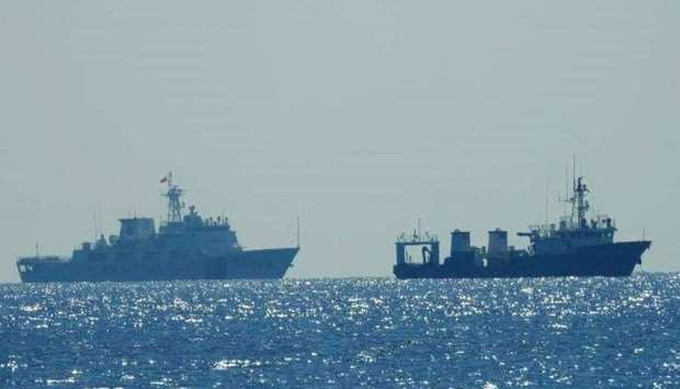 A Chinese Coast Guard patrol ship (L) is seen near an unidentified vessel at South China Sea, in a h
