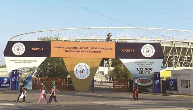 People make their way past the main entrance of the Narendra Modi Stadium, a venue where cricket mat