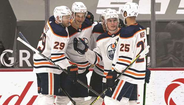 Tyson Barrie (second right) of the Edmonton Oilers is congratulated by teammates Leon Draisaitl, Jes