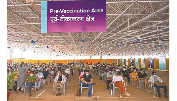 People wait to get a dose of the Covishield vaccine against Covid-19 at the vaccination centre of BL