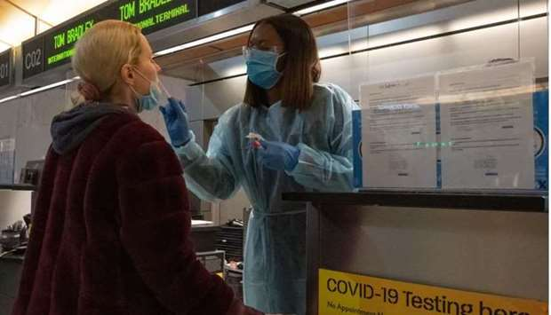 A traveller receives a nasal swab from a nurse at a Covid-19 test site inside Terminal B at Los Ange