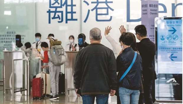 People wave in the departures hall at the Hong Kong International Airport. As Singapore's government