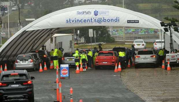 Medical officers conduct a mass Covid-19 testing at a parking lot on Bondi Beach in Sydney as admini
