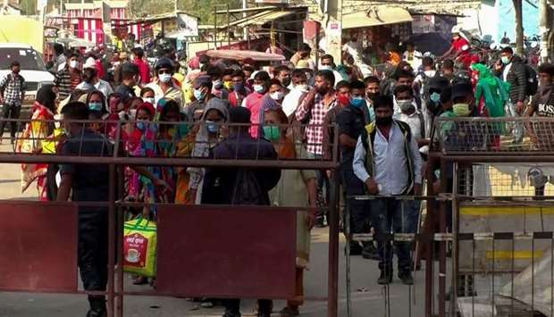 Nepali migrants workers wait to walk across the India-Nepal border as they return to Nepal, in Jamun