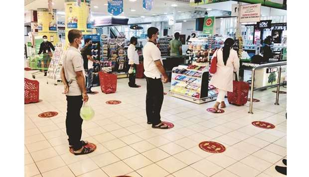 Shoppers maintain social distancing while waiting at the check-out counter of a hypermarket in Doha.