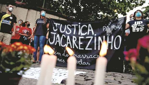 People attend a protest against police violence, outside the Jacarezinho slum, following a police op