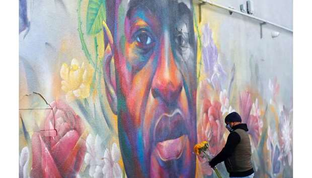 (File photo) A man places flowers at a mural of George Floyd after the verdict in the trial of forme