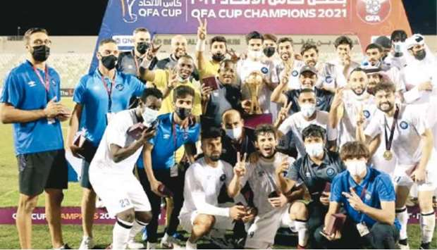 Al Sailiya players and support staff celebrate after winning the QFA Cup.
