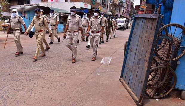 Police personnel patrol along a deserted street during restrictions imposed as a preventive measure