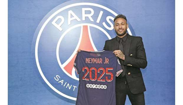 Neymar poses with a Paris Saint-Germain jersey after signing a new contract yesterday.