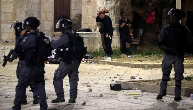 Palestinians take cover during clashes with Israeli police at the compound that houses Al-Aqsa Mosqu