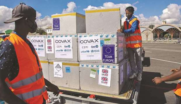 Workers handle boxes of Oxford/AstraZeneca Covid-19 vaccines,after these arrived by plane at the Iva