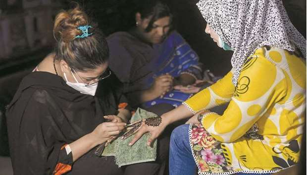 A girl gets her hand decorated with henna paste at a marketplace ahead of the Eid al-Fitr festivitie