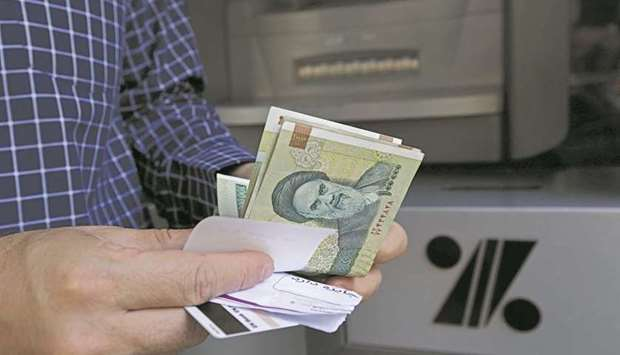 A man withdraws Iranian rial notes from an automated teller machine in the capital Tehran (file). Ir