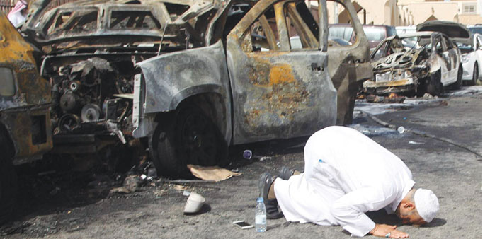 The cousin of a victim prays at the site of the suicide bombing in Dammam yesterday.